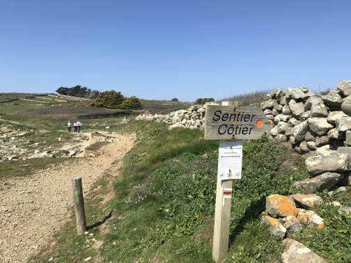 """A rough dirt-and-rock trail curves away roughly to the west, with three people walking in the distance.  In the foreground is a sign reading """"Sentier Côtier""""; on the signpost is a white stripe above a red stripe above a right-pointing arrow.  To the right of the sign is a rough rock wall; stone walls define rectangular fields in the far distance."""