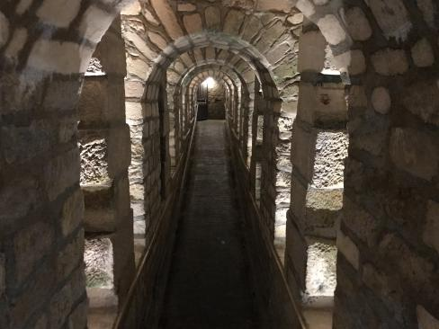 Looking down a narrow, low, stone passage, lit from the niches between the many arches.  The passage slopes up gradually; at the far end, some kind of gate stands open, with a light by it.
