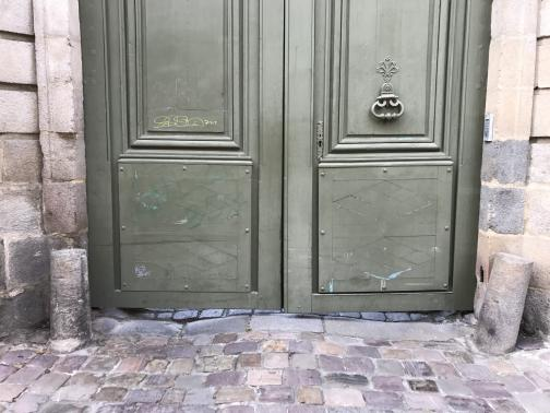 A large pair of doors is closed to the north, painted a uniform olive green, with a bit of yellow graffiti on the left and a handle or knocker on the right.  Only the bottom five feet or so are visible; it is unclear how tall they are.  The building is pale stone; the ground is cobblestones, and a pair of depressions shows where cars and wagons have passed through.