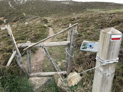 A rustic wooden gate is in a barbed-wire fence.  It is closed, and opens into the field, away from the viewer.  On the near side is a sturdy post.  A rope is tied to the gate and the post, and in the middle between the two is tied a heavy rock.  The trail is visible winding through the hilly field on the other side of the gate; otherwise, the field is filled with scrubby brush and occasional rocks.
