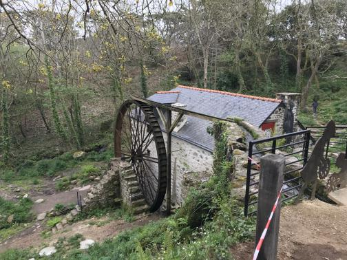 A millhouse in good condition is mostly visible below.  The waterwheel is prominently visible on the side of the house, with stone steps leading up to the other end of its axle.  Looking carefully, we can see a trough to carry water from a nearby stream to pour down onto the top of the wheel, to drive it, but no water is visible — the mill is not active.