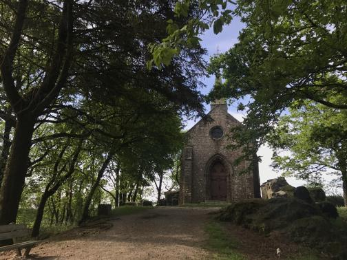 A wide dirt path leads to a tall chapel, seen end-on; trees on either side of the path lean over and provide shade.  At the front left is a wooden bench at the side of the path; to the right are low rocks.  The chapel is made of neat stone, with a peaked pair of double doors below a small, round window.  Nothing can be seen beyond the chapel, suggesting it is perched at the top of a slope.
