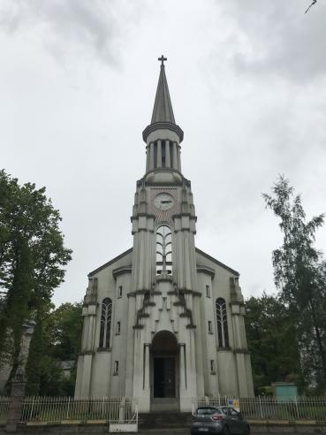 To the south stands a tall white church; its symmetry and the details of its design place it firmly in the Art Deco style.  Rays radiate from a clock halfway up the steeple, while tall, narrow windows flank the entry porch.  Steps lead up to it from the street, with a single compact car parked in front.