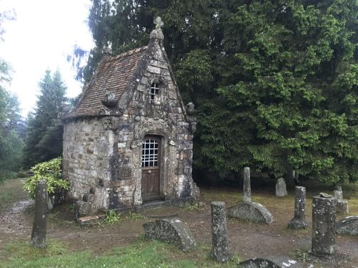 A tiny stone chapel, not much more than six feet square, stands to the south-southwest.  Behind is a large evergreen; around it the ground is muddy, with a path marked by stone or concrete pillars and low barriers, all spotted with lichen.  The chapel has a low wooden door with a metal grille as a window; a smaller window is above the door, under the steeply-peaked roof.