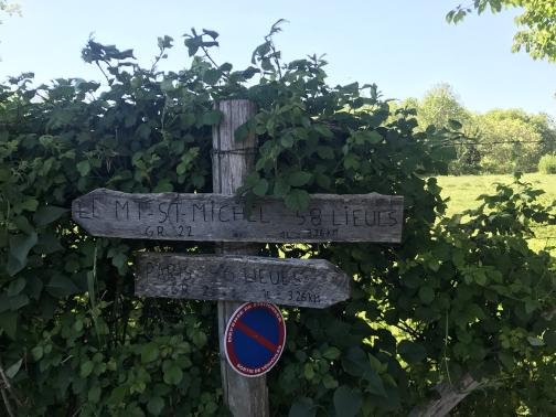 """A rough wooden post to the east is nearly engulfed in something resembling raspberry vines.  Nailed to the post are two weathered wooden arrows with writing.  Below the arrows is a round blue placard with a red ring-and-slash (a classic """"forbidden"""" sign), reading """"DÉFENSE DE STATIONNER / SORTIE DE VÉHICULES"""" (""""no parking / vehicle exit"""").  A closer look shows that the post is part of a barbed wire fence."""
