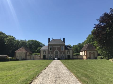 A gravel path leads south-southeast through a well-groomed lawn to a brick gatehouse, two stories plus a tall roof.  Symmetrically to either side are what look like extensions to the gatehouse, then a wall, and then smaller buildings at the corners, suggesting a compound that stretches behind.  A single car is parked by the building, pointing towards us.  Trees surround the lawn and property; the sky is perfectly blue.