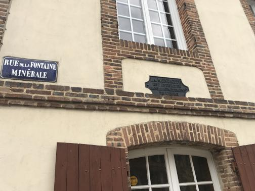 """A brick-and-plaster building is close to the west.  We can see the top of a window (the bricks above it form a gentle arch), and the bottom of the window on the floor above.  To the left is a street sign reading """"Rue de la Fontaine Minérale"""" (""""Mineral Spring Road""""), while a metal plaque with embossed writing is mounted between the windows."""