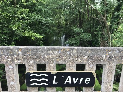"""In the foreground is a concrete guardrail with a black sign across the vertical bars, reading """"L'Avre"""" with three wavy lines to the left, suggestive of flowing water.  To the east below is a small river.  The near parts of the river, through the rail, have some sort of green plant growing underwater; trees reach over it, forming a tunnel for the entire visible length."""