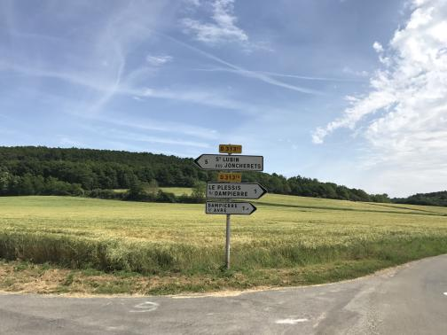 """At the corner of two paved roads to the southeast, a signpost stands at the edge of a field.  From top to bottom, there is a yellow sign reading """"D 313¹¹"""", above a white arrow sign pointing left and reading """"5—St Lubin des Joncherets""""; then a yellow sign reading """"D 313¹⁵"""", above two white arrow signs pointing right, reading """"Le Plessis s/ Dampierre—1"""" and """"Dampierre s/ Avre—1.8"""".  The field behind the sign looks recently mown; it rises up gradually to a wooded hill in the distance.  The sky is blue with a few lazy contrails and, to the right, some white clouds."""