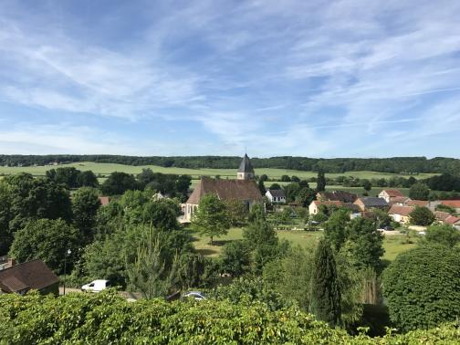 Below to the southwest is a small village, with green fields beyond.  In the center of the photo is a church; perhaps a score of houses and other buildings are also visible, mostly to the right.  The left side of the photo, and much of the foreground, is full of trees, and trees run along the ridge at the horizon.  In the foreground below is the hint of a road running left to right, with cars parked on it; in the close foreground is a bush or hedge.  The sky has wispy clouds.
