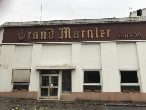 """To the northwest stands a white, two-story commercial building, its windows and glass door dark and empty.  Flowerboxes in the windows are also empty.  A dark brown sign stretches the building's width, reading """"Grand Marnier Liqvor"""" in tarnished logotype.  The building opens onto a cobblestone sidewalk next to a cobblestone road, both damp."""