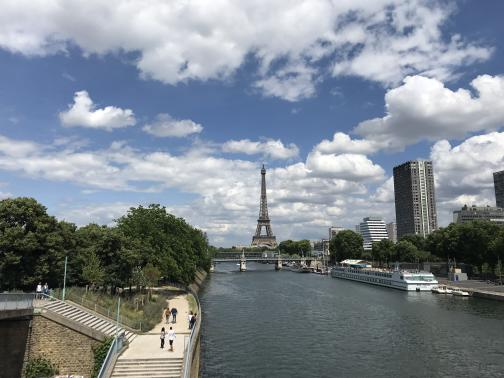 A river runs from the center of the photo to the bottom.  Beyond, to the northeast, the Eiffel Tower stands tall on the horizon.  On the right side of the river, a long, low barge is docked; behind it are trees and a handful office buildings.  To the left side, a broad sidewalk runs below, winding away from the river through trees as it heads away.  The sky above is partly cloudy, but overcast in the distance.