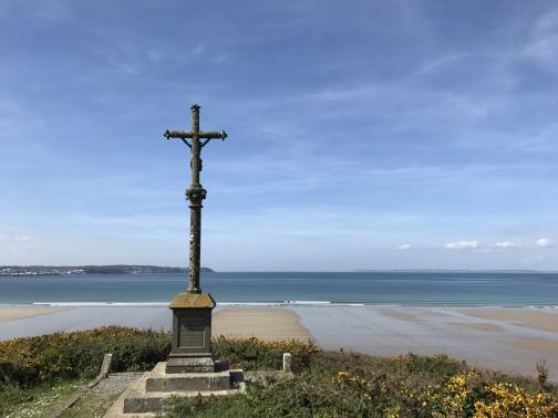 A crucifix stands atop a tall pedestal, elaborate but weathered.  Surrounding it at a short distance is gorse.  Beyond to the west is a beach of wet sand, and the Bay of Douarnenez, and beyond that at the left is a headland.