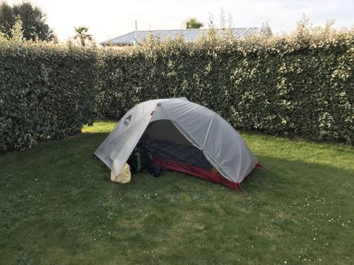 A small, one-person tent is set up on a patch of lawn.  The tent itself is red with a mesh door panel, but is mostly hidden under a pale grey rain fly.  A backpack and yellow cloth bag are tucked under the fly next to the tent.  Behind the tent on two sides are hedges, offering privacy from other pitches on the campsite.