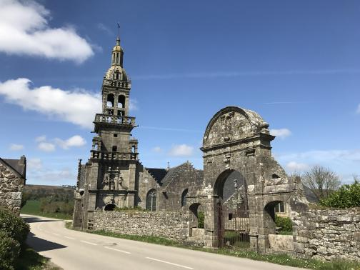 An elaborately-decorated stone chapel is by the side of a road.  Its yard is enclosed by a stone wall, with an arched gate in the middle.  The chapel's bell tower has balconies and is partially open to the air.