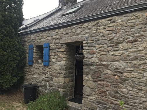 This is part of a long stone building to the east; the roof is sloped, with two skylights barely visible from this angle.  The door has a thick stone slab for a lintel; a small window nearby has neat blue shutters open to either side.  Both the window and door let us see that the wall is perhaps a foot-and-a-half thick.