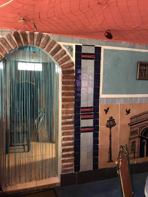 """A brick-lined archway with a bead curtain leads to the restaurant's back rooms.  The ceiling is red-orange, and tiled walls are blue and yellow.  Next to the arch are four tile markers at different heights, labeled """"28.02.2010"""" at a little less than three feet from the floor, up to """"24.12.2013"""" near the top of the arch."""
