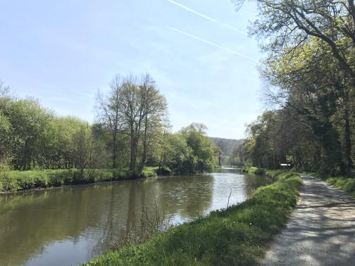 A broad, flat canal runs to the south.  Grass separates the canal from a paved trail on the near side; the trail is lined and shaded by trees.  Trees line the opposite side of the canal, with no trail visible there.