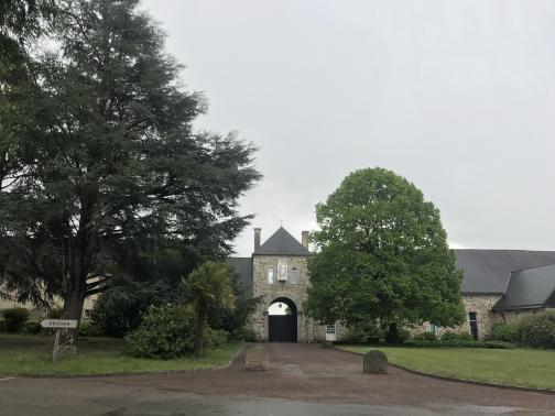 A stone building, one story plus a peaked roof, stretches the width of the photo.  In the center is a taller tower or gatehouse, with an arched gate in the middle leading through southeast to perhaps a courtyard; on top of this is a small cross.  A drive paved drive leads to the gate from the road in front.  Two large trees and a lawn fill the space between road and building.  The sky above is pale grey.