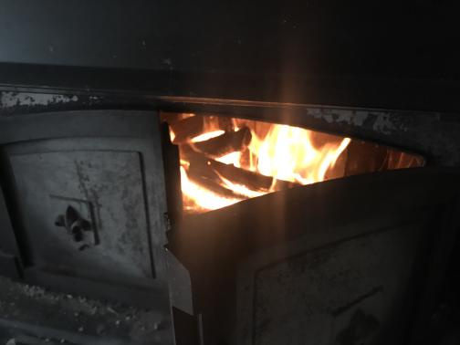A black wood-burning stove has one door open, revealing a glowing orange fire inside.
