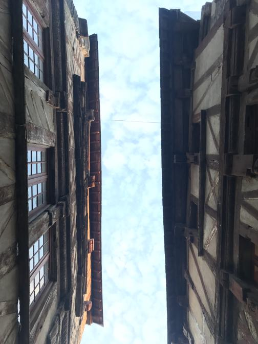 Looking straight up from between two timbered buildings, we see a cloudy sky through the narrow gap at the top.