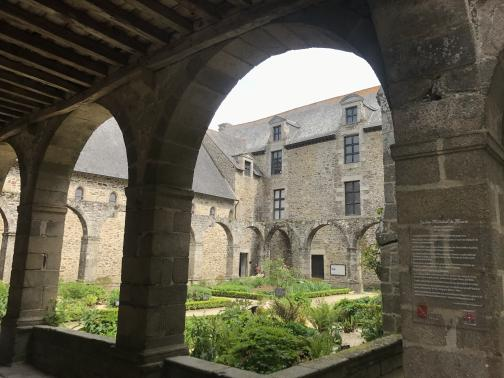 """From under a shady arched colonnade, we look at neatly-groomed flowerbeds in a courtyard.  The far right side of the courtyard is defined by a four-story-tall stone building; the left side is only three stories, both with windows and steep roofs.  A placard on the nearest pillar describes the courtyard—""""Jardin Médiéval de Marie"""" (""""medieval garden of Mary"""") can be read, but the rest is difficult to make out."""