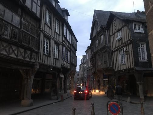 At dusk, a small car is driving away to the east on a cobblestone road, between rows of medieval buildings.  The buildings reach over the sidewalks on pillars, and are timber-framed with something like plaster between timbers, two or three stories above the ground floor.  Two pedestrians are barely visible in the dimming light.