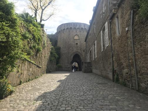 A steep cobblestone road climbs to the south-southwest, ending at a broad, round stone tower.  Pedestrians can continue through a dark, arched tunnel to the other side.  The tower has few windows; its entire look is quite medieval.  To the left is a tall stone wall, with ivy growing over much of it; to the right are stone buildings, with at most one door visible (though they have more windows than the tower).