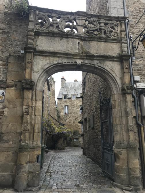 """Through an arch, a narrow cobblestone road runs to the north-northwest between stone buildings.  It either turns to the right, or ends in a courtyard that extends that direction.  Next to the arch, on the right to the right, is a small white sign reading """"Rue Haute-Voie""""."""