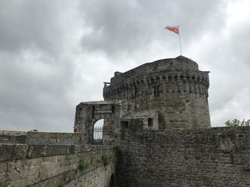 Looking west from what must be the top of one of the town's walls, the tops of two walls meet in front of a heavy stone tower.  An arched gate leads to the area around the tower; from the top of the tower, a white and red flag flies in the wind.  The sky is overcast and grey.