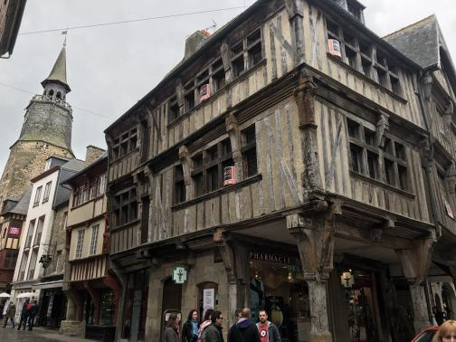 A three- or four-story building, wood-framed with plaster between the beams, extends out on pillars beyond its ground floor.  Many corners that were originally right angles have sagged into slightly new configurations.  In the upper windows are red and black signs, perhaps for-lease signs.  People are strolling in front and down the street to the south, where there is another half-timbered building along with newer ones.  Perhaps a block away is a stone tower with a walkway near the top.  The sky is grey.