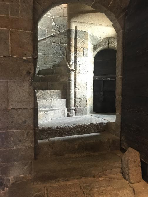 Four steps climb through an interior archway to a landing, well-lit from an unseen window to the right.  A tight spiral staircase climbs up to the right from the landing; a dark arch leads under it.  Ropes fed through rings form a handrail for the spiral staircase; other than that, all the construction is grey stone.