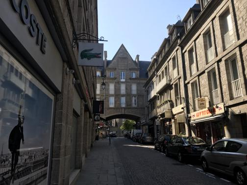 """Four-story stone buildings line the cobblestone street.  Towards the end of the street, a building stretches overhead, with an arched tunnel under.  On the left side, a white sign with an alligator hangs overhead, with """"—COSTE"""" visible above shop's window.  Cars are parked on the opposite side of the street.  Everything looks neat, clean, and regular."""
