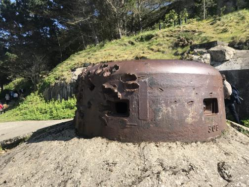A low metal turret, rust red, squats in a concrete setting.  Two rectangular holes could open to the interior.  On the left side are massive dents and scars from powerful projectiles, revealing that the turret's metal is at least several inches thick.  Behind it to the southeast, a grassy slope leads up.  Pedestrians are visible behind and farther away to the left.