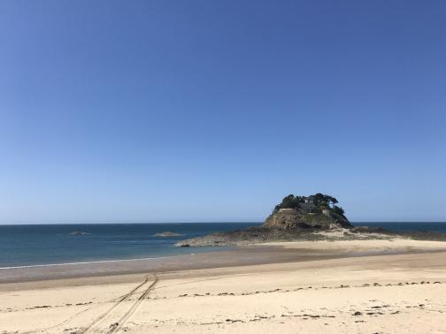 To the northwest across the sand, a rocky promontory rises up at the water's edge; at high tide, it is probably cut off from the land.  On top are what look like old fortifications, with wind-blown trees and a well-kept house inside.  The sky overhead is a rich, perfect blue.
