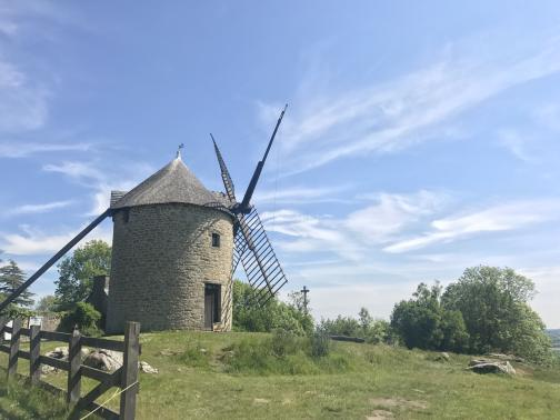At the top of a hill, a round stone windmill in good repair is to the southeast.  The blades on the right are only frames, with no canvas to actually catch the wind, but it looks in good repair otherwise.  On the left (back) of the mill, some kind of beam stretches diagonally from the base of the conical roof to the ground; perhaps it is a chute for milled grain.  A wooden fence is at the left of the photo, and trees are scattered around the far side of the mill.  A small calvaire (crucifix) stands in front of the mill's blades.  The sky is blue with scattered wispy clouds.
