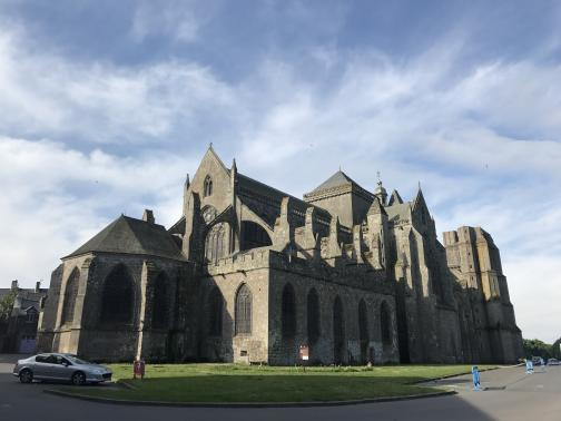 To the south-southwest, a massive stone cathedral sits by a small lawn.  The cathedral looks like it has accumulated various buttresses, towers, and spires over the centuries; it is difficult to determine the exact history of the construction.  By the lawn, a single car is parked in a parking lot; overhead are three small birds and some wispy clouds.