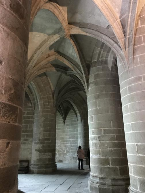In this stone room, the pillars are shorter and much more massive, holding up another rib vault ceiling.  Two other tourists are at the far end of the space, near where light is coming in from two unseen windows.