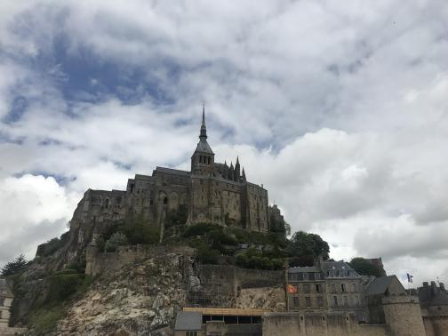 Ahead to the north, we can see the abbey of Mont-Saint-Michel towering atop its rocky island.  The top spire catches the eye; a closer look reveals the golden statue at the pinnacle.  Below the walls of the abbey, the town's walls and a few buildings can be seen, and then the rock of the island itself.  A few trees are wedged here and there; the sky is mostly cloudy.