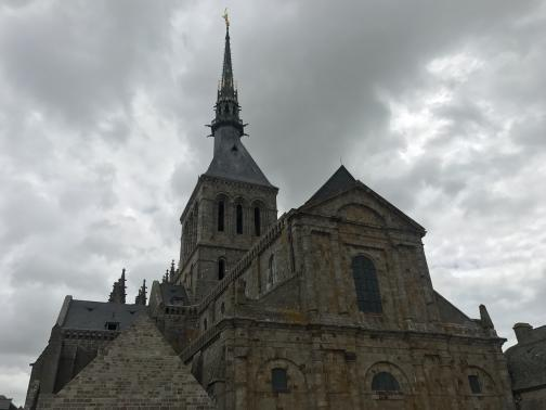 The bulk of the abbey stands to the south; from here, it looks much like any very large church, though its spire is especially tall, and is topped by a golden statue.  A few windows are visible, but mostly the structure impresses due to its size, not its grace.