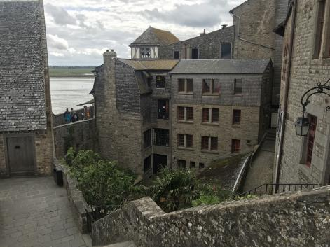 A stone walkway, perhaps the top of a thick defensive wall, steps down to the southeast to some sort of structure, perhaps a tower.  Beyond it is another stretch of wall, and beyond that is water and tidal flats.  Within the walls are tall buildings of the same stone, apparently empty, along with a narrow elevated walkway and a few small trees or bushes.